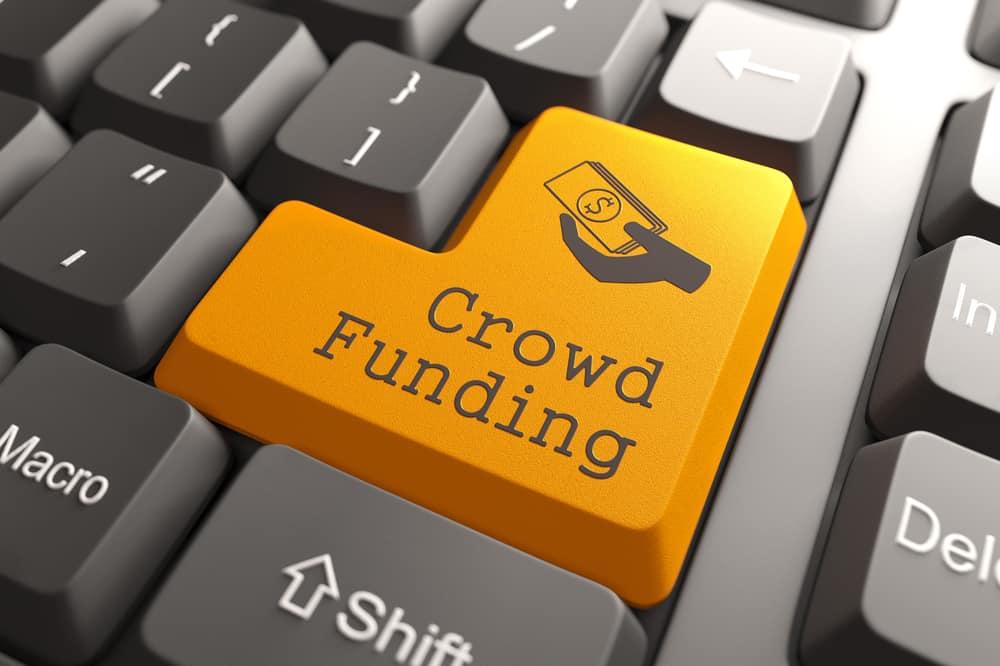 Botón de financiación de multitud naranja en el teclado de la computadora. Concepto de Internet.