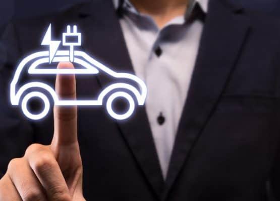 Empresario eligiendo el botón del coche eléctrico en la pantalla virtual