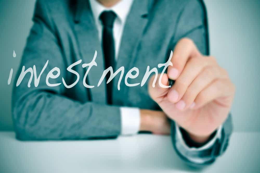 empresario sentado en un escritorio escribiendo la palabra inversión en primer plano