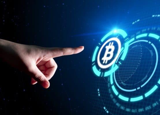 Dedo índice pulsando un botón de bitcoin