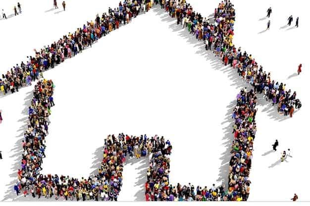 Gente agrupada formando la silueta de una casa