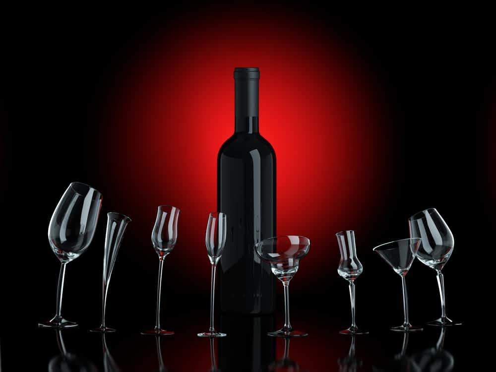 Botella de vino con fondo negro y rojo y copas de vino diferentes en fila
