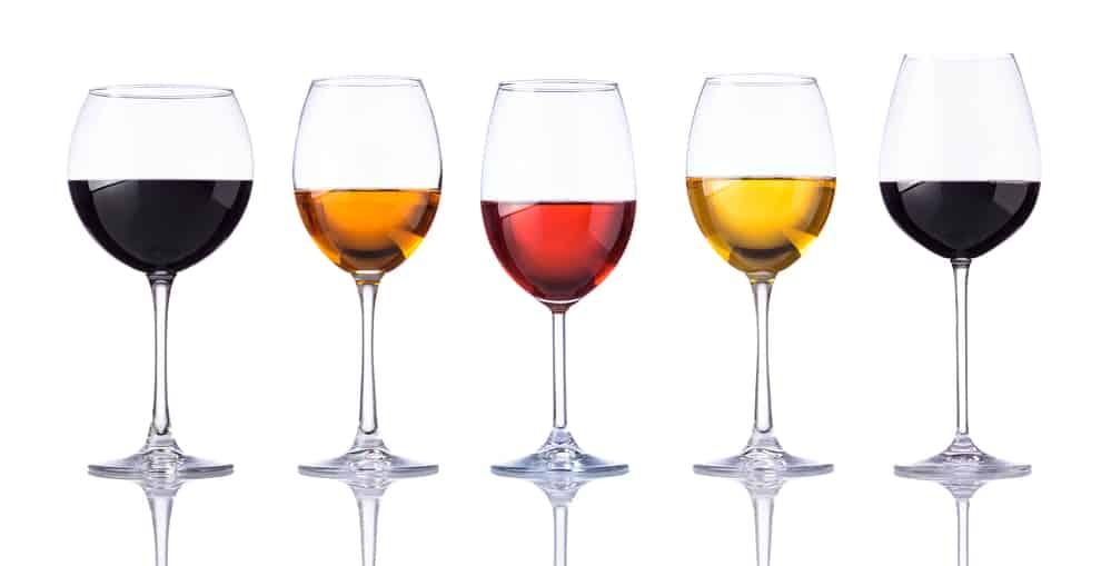 Copas de vino con vino rosado, tinto y blanco aislado sobre fondo blanco.