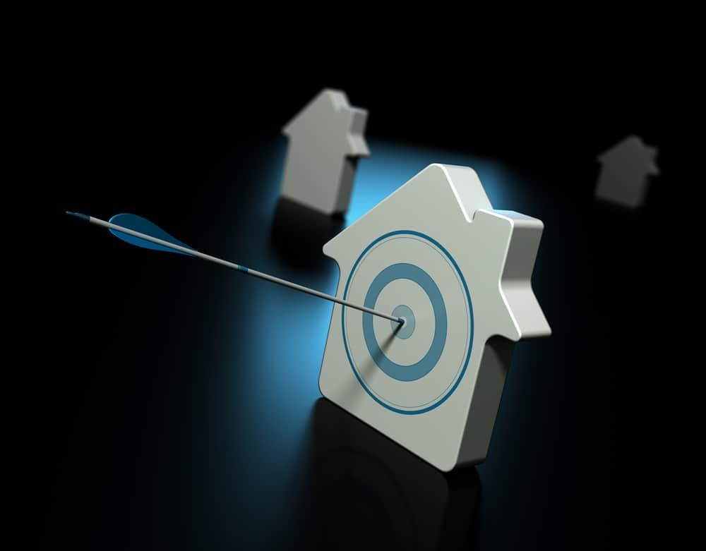 Tres casas sobre negro con reflejo azul, la primera casa está atravesada por una flecha en el centro del objetivo, las otras propiedades en el fondo están borrosas, símbolo de búsqueda de bienes raíces y propiedades