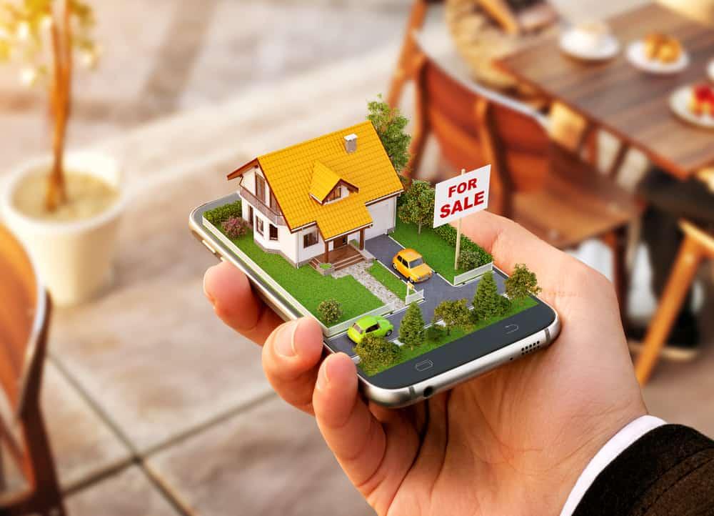 Mano con móvil y una casa y un césped en 3d