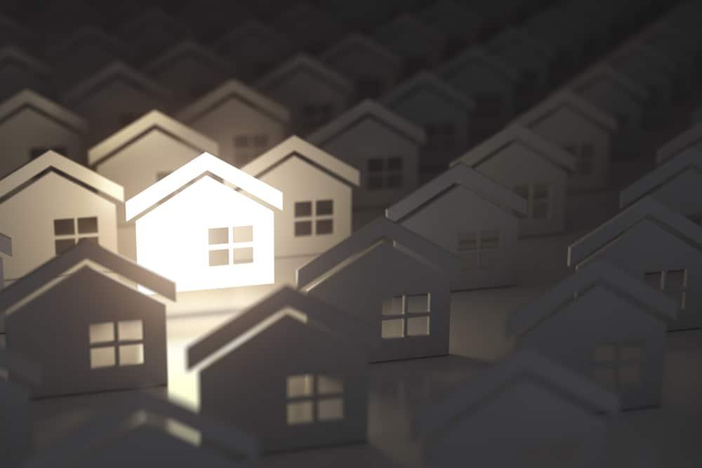 Signo de casa de iluminación única en grupo de casas. Fondo de concepto de industria de propiedad inmobiliaria. Ilustración 3d