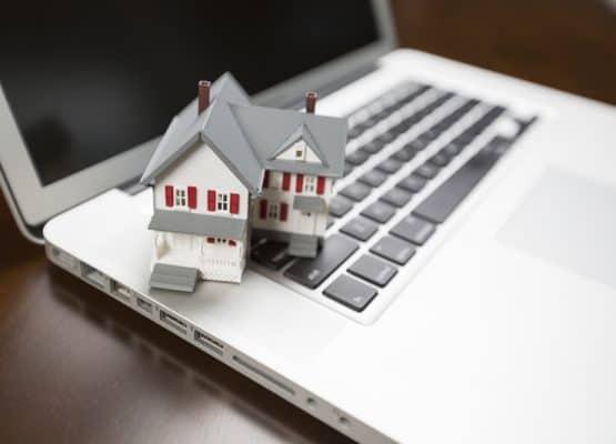 Casa en miniatura y computadora portátil descansando sobre el escritorio.