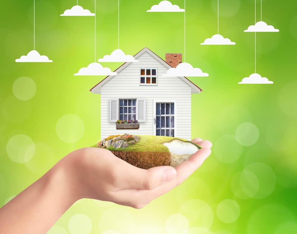 Mano con una casa en un trozo de tierra con césped