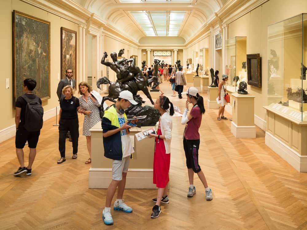 Visitantes admirando esculturas de Auguste Rodin y pinturas en el Museo Metropolitano de Arte de Manhattan